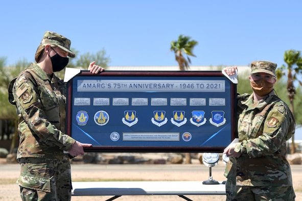 A picture of Brig. Gen. von Hoffman and Colonel Barnard holding up a plaque to commemorate the AMARG's 75th Anniversary.
