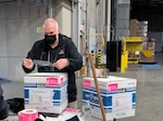 White man holds a label over top of a box he's preparing to ship.