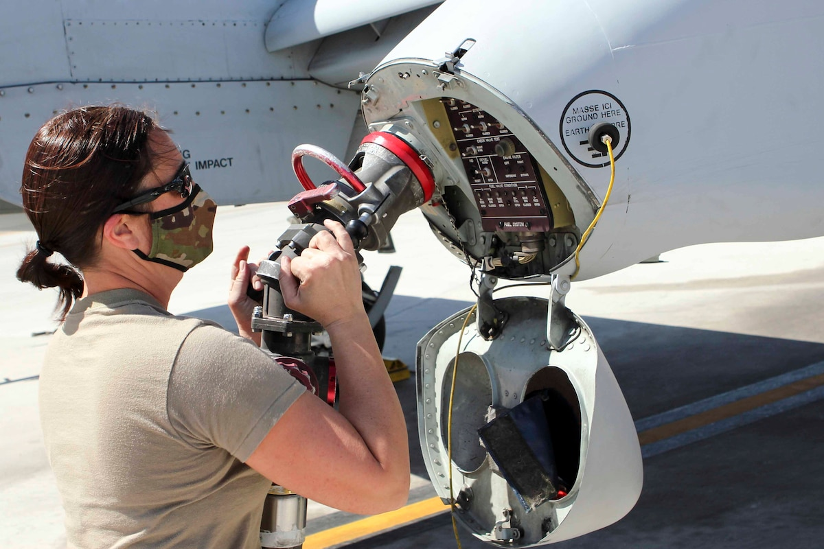 An airman holds a fuel hose next to an aircraft.