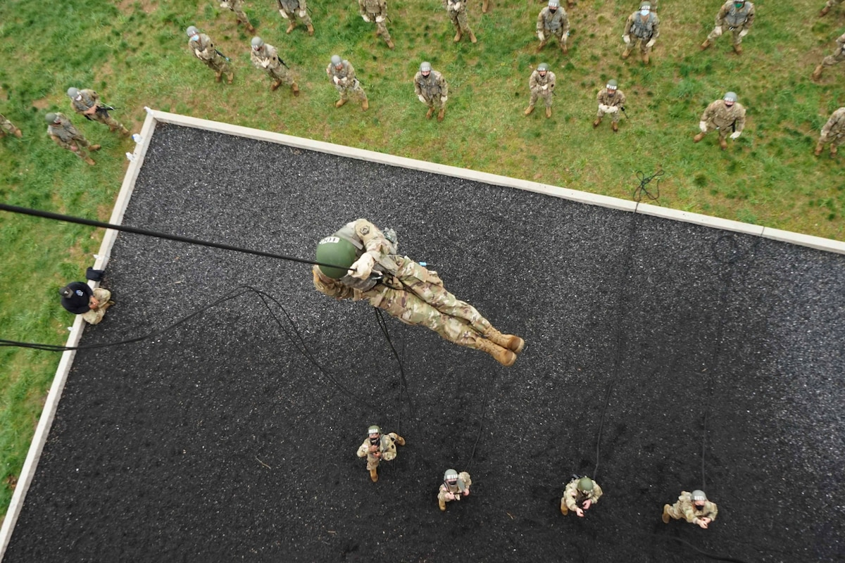 A soldier rappels down on a rope as others watch from below.