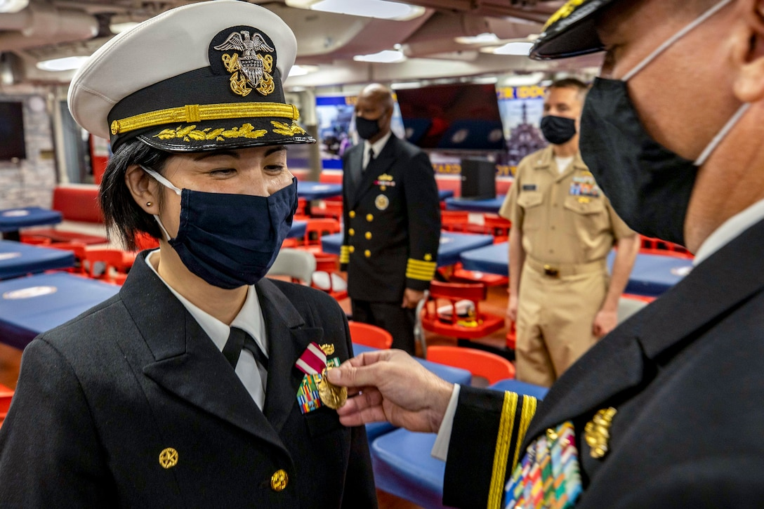 A sailor wearing a mask smiles as another sailor puts a medal on her uniform.