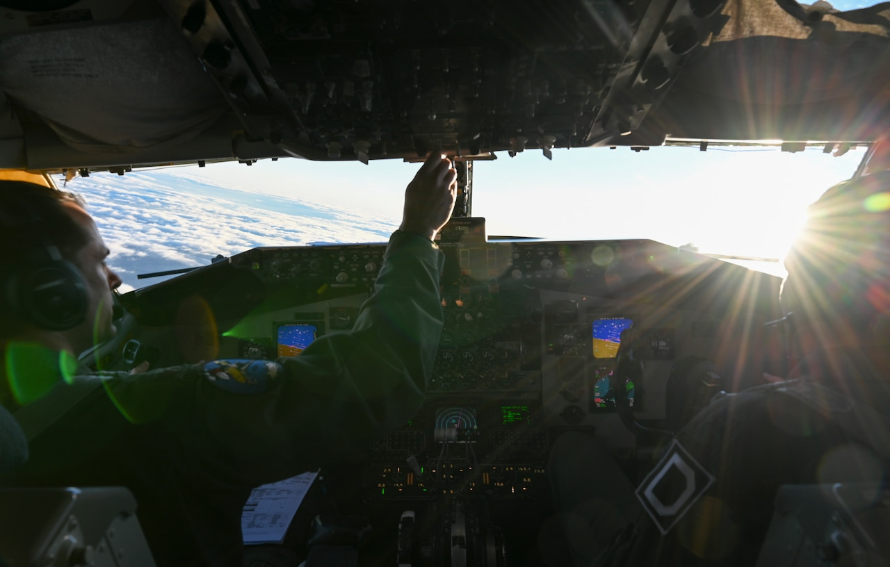 Airmen, shown from behind, sit in the darkened cockpit of an aircraft in flight.