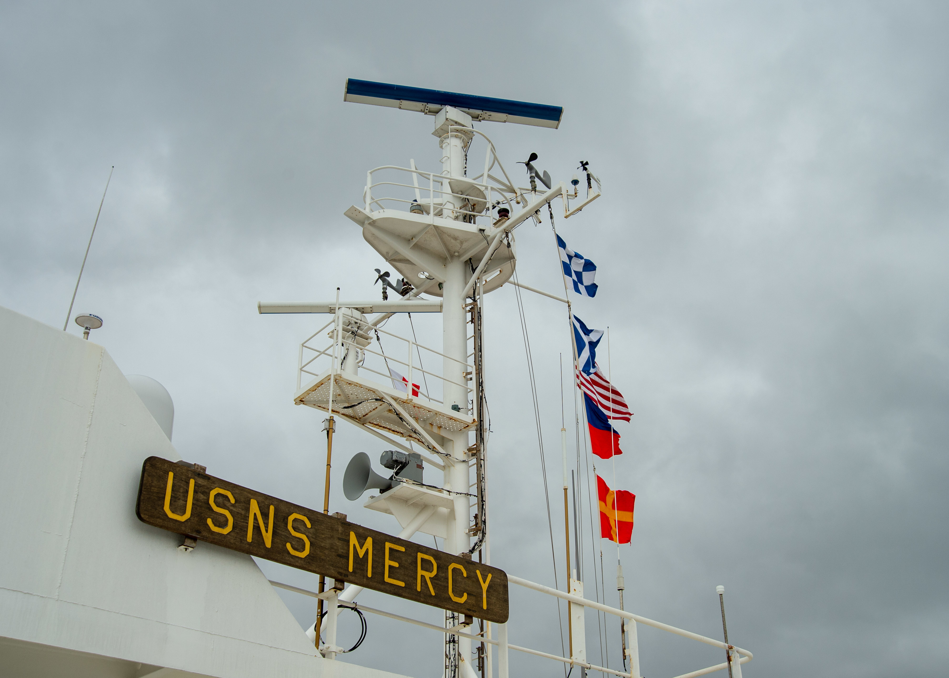 A photo of the mast of the Military Sealift Command hospital ship USNS Mercy (T-AH 19) with underway pennants.