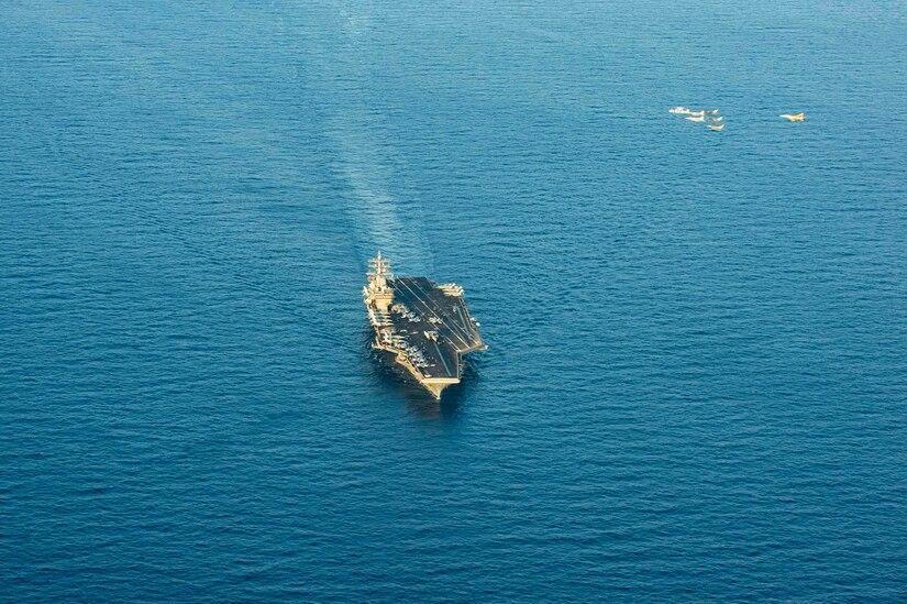 A carrier strike group sails across the ocean.