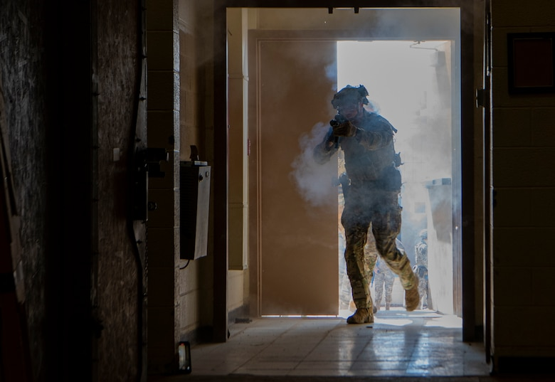Airman enters building holding a rifle during training.
