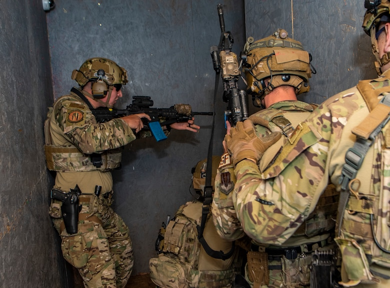 Airmen in a hallway holding rifles during a exercise.