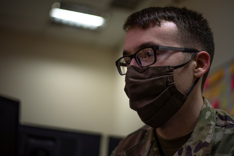 A photo of an Airman looking at a computer