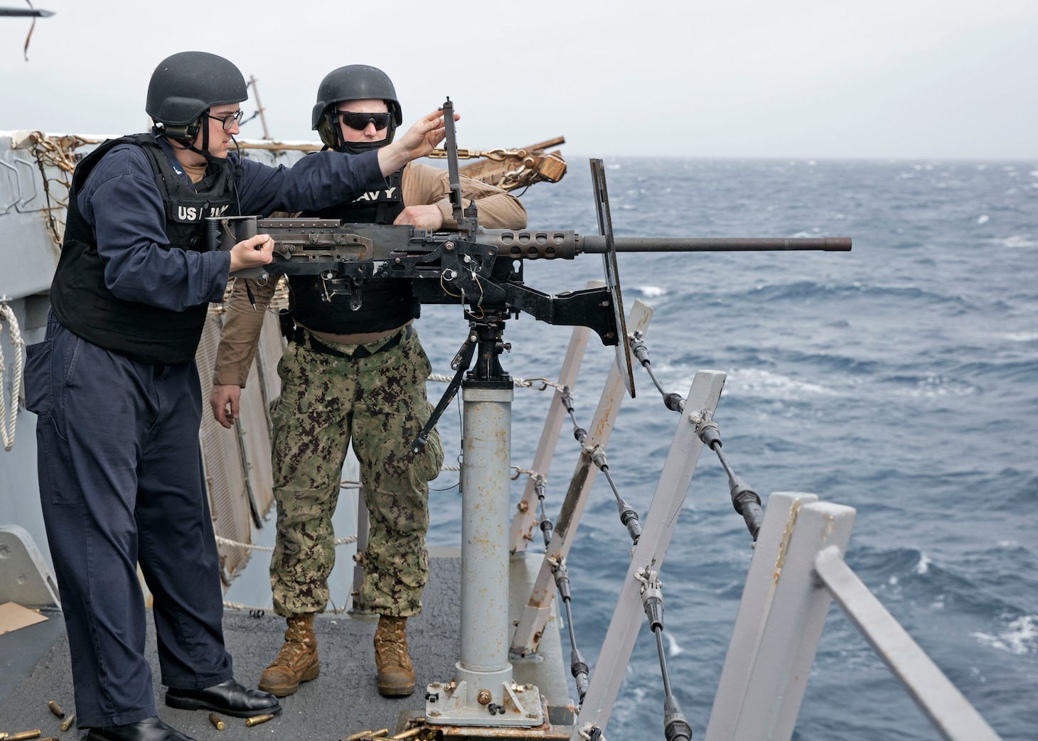 Gunner's Mate 2nd Class Dylan Harris, right, and Logistics Specialist 3rd Class Aaron Scott assigned to the amphibious transport dock ship USS San Antonio (LPD 17) inspect a M-2 .50 caliber machine gun during a live-fire exercise on the ship's flight deck, April 1, 2021.
