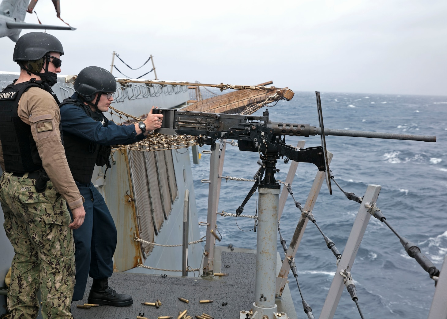 Seaman Ethan Valentine , right, and Gunner's Mate 2nd Class Dylan Harris assigned to the amphibious transport dock ship USS San Antonio (LPD 17) watches as Valentine fires a M-2 .50 caliber machine gun on the ship's flight deck, April 1, 2021.
