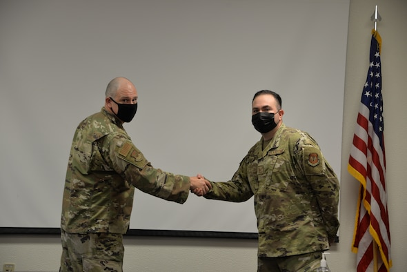 Two Airmen shaking hands.