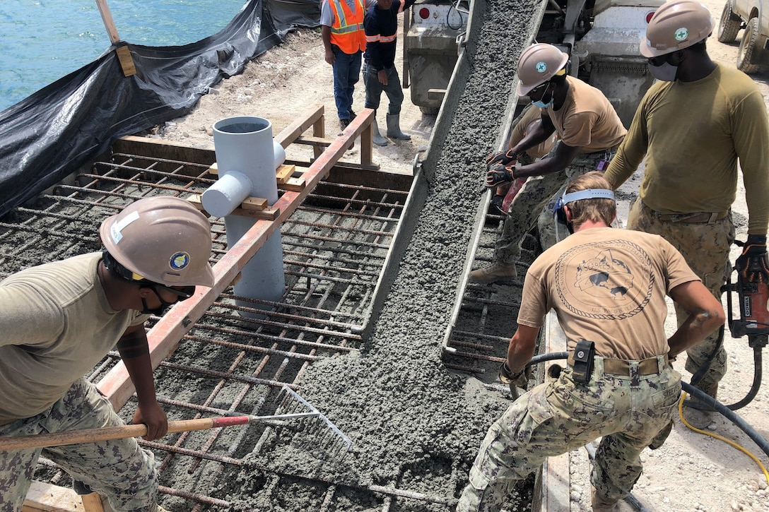A group of Navy Seabees spread concrete on a platform.