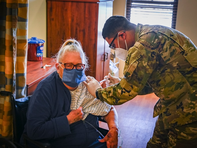 """Spc. Andres Salgado, 142nd Medical Company combat medic, vaccinates Marilyn Degnan, a resident at the Mary Wade Home in New Haven, Connecticut, April 9, 2021. The Connecticut National Guard assisted the Connecticut Department of Public Health in providing COVID-19 vaccinations to nursing home residents and staff through """"Operation Matchmaker."""""""