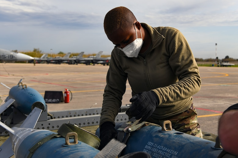 Senior Airman Sydney Williams, 31st Munitions Squadron (MUNS) line delivery crew chief, secures an inert bomb onto a trailer at Andravida Air Base, Greece, April 13, 2021. The 31st MUNS, along with other units from the 31st Fighter Wing, participated in INIOCHOS 21, a Hellenic air force-led, joint force exercise. (U.S. Air Force photo by Airman 1st Class Thomas S. Keisler IV)