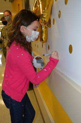 Seven-year-old Sailor Parker writes her name on a wall sticker