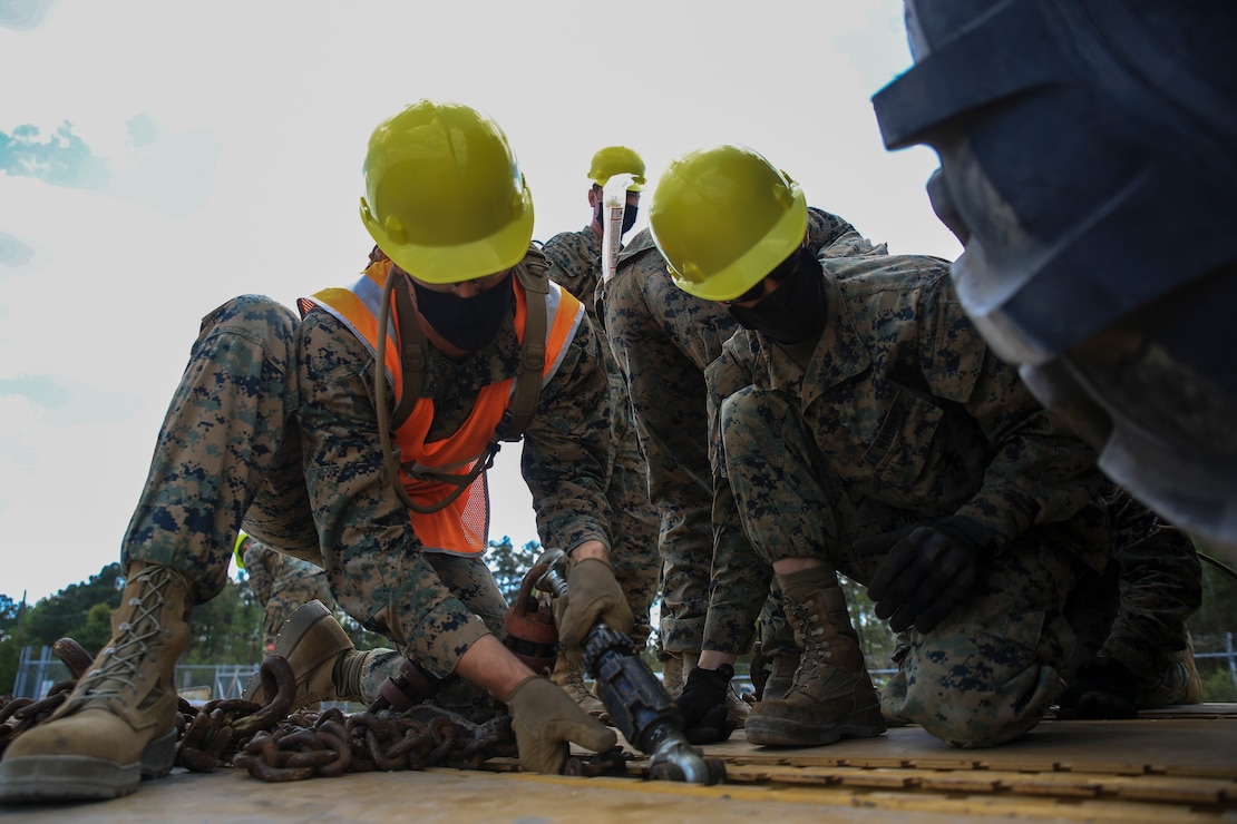 U.S. Marines tie down a vehicle onto a rail car in preparation for Operational Logistics Exercise on Marine Corps Base Camp Lejeune, N.C., April 13.