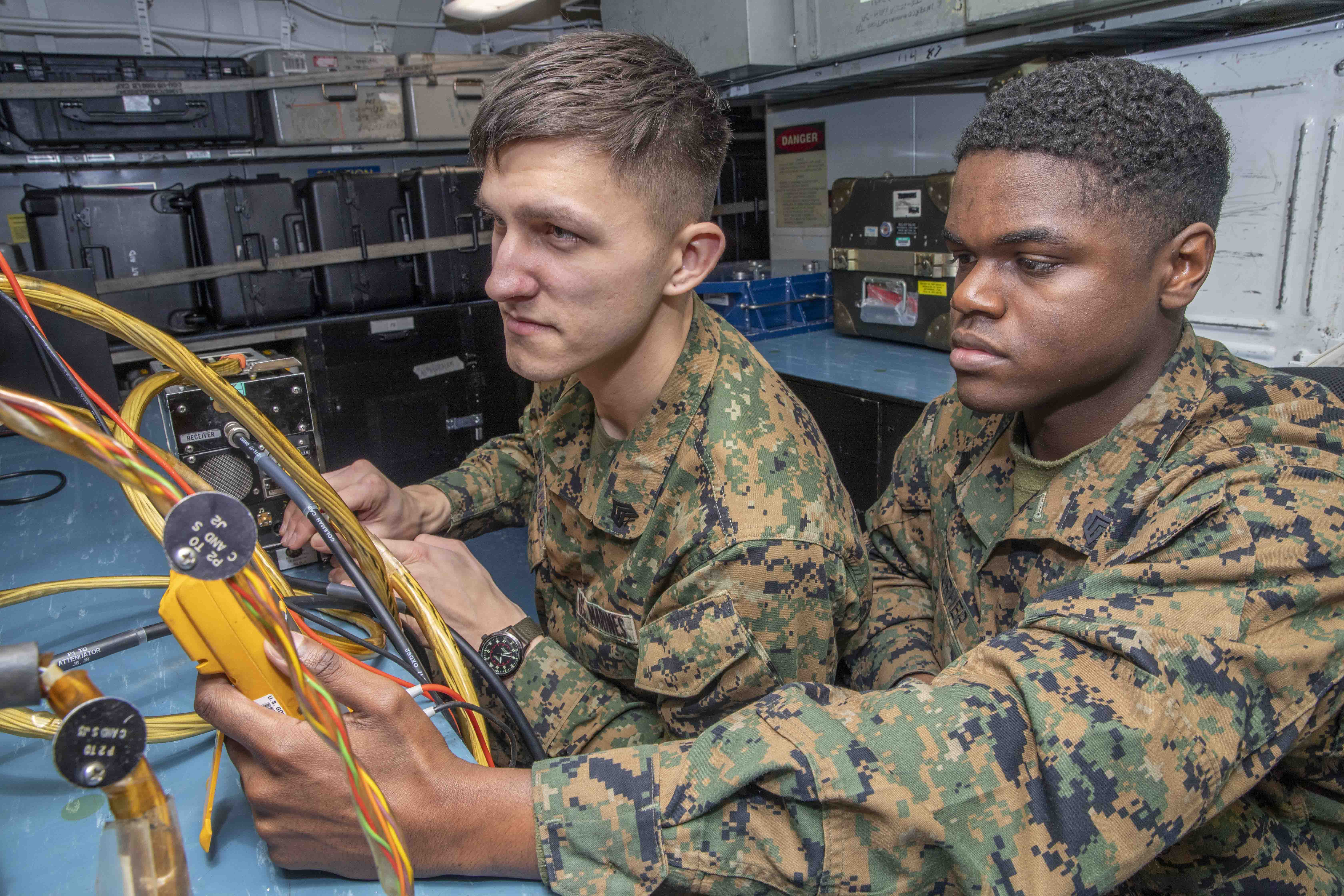 Sgt. Devin Salamaca, left, and Sgt. Shaquille Turner, both assigned to the 24th Marine Expeditionary Unit (24th MEU), perform intermediate maintenance on a radar altimeter onboard the Wasp-class amphibious assault ship USS Iwo Jima (LHD 7).