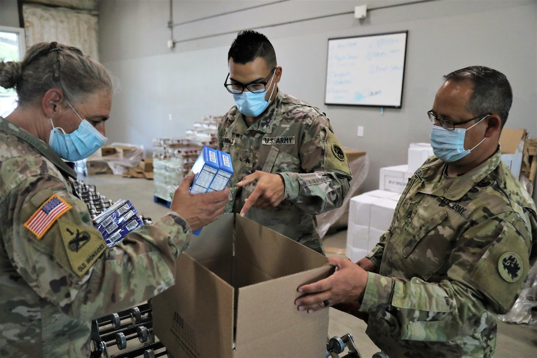 Three soldiers put food in a box.