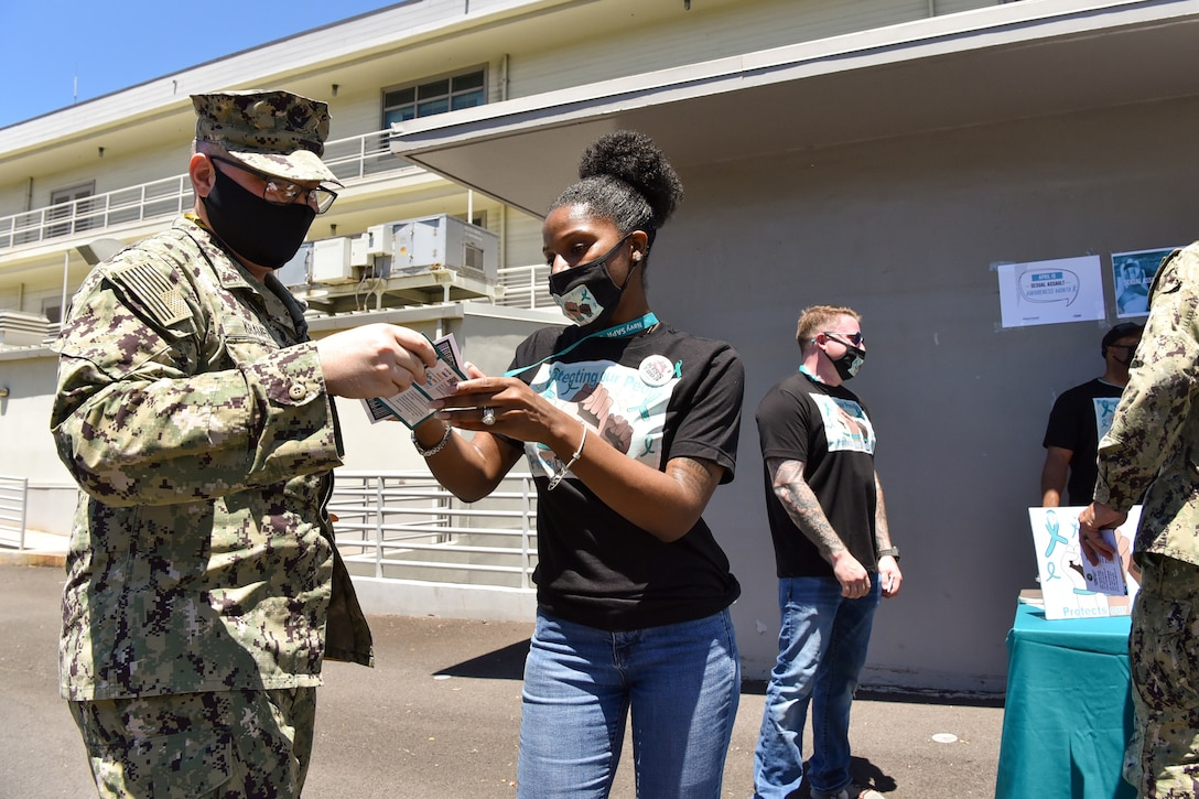 A sailor in civilian clothes speaks to another sailor while they look a some pieces of paper.