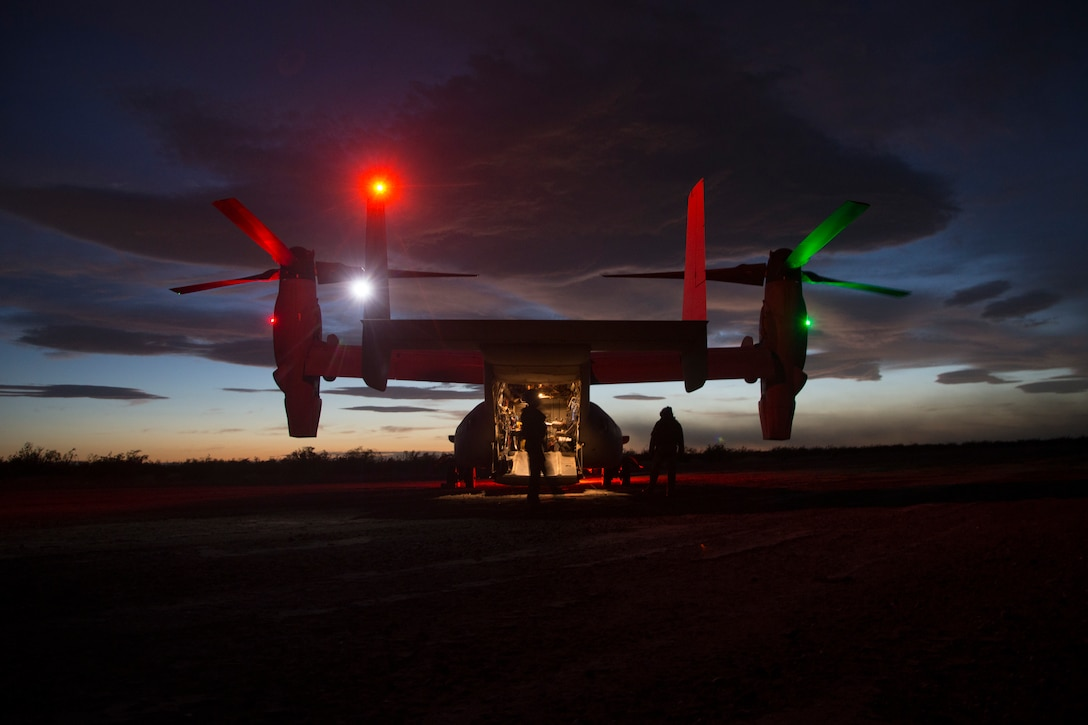 An aircraft sits on a tarmac at night illuminated by red and green lights.