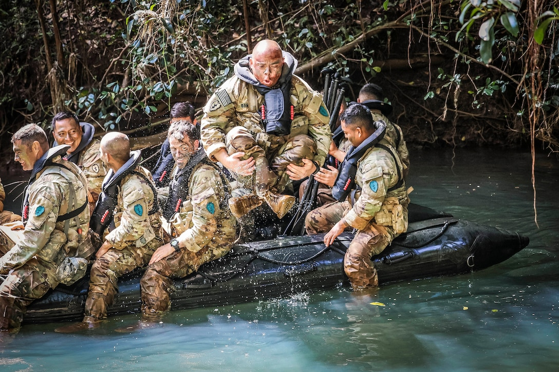 A soldier jumps out of a small boat as fellow soldiers watch.