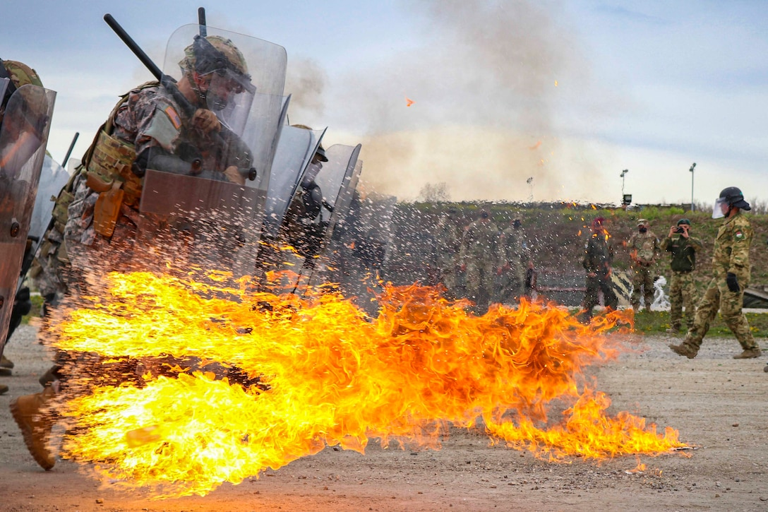 Soldiers holding plastic shields run through fire.