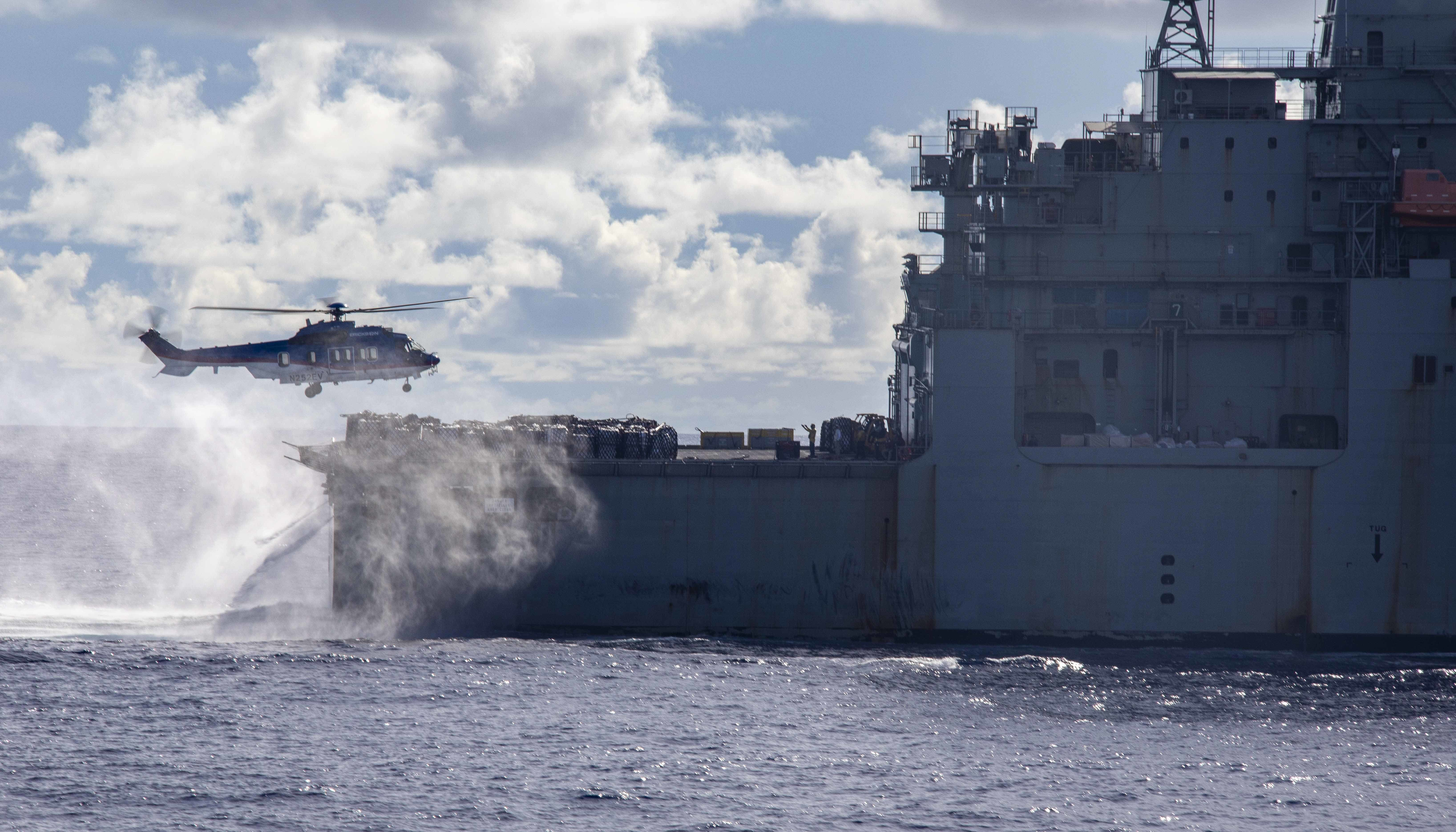 A U.S. Airbus H225 Super Puma helicopter conducts a replenishment-at-sea with the dry cargo and ammunition ship USNS Alan Shepard (T-AKE 3) and the amphibious assault ship USS Makin Island (LHD 8).