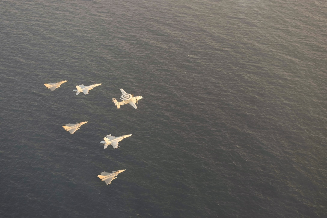 U.S. and French aircraft fly in formation over a body of water.