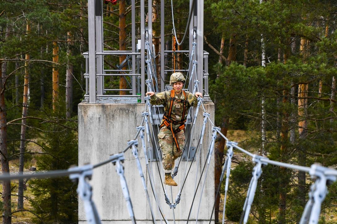A soldier crosses a cable bridge.