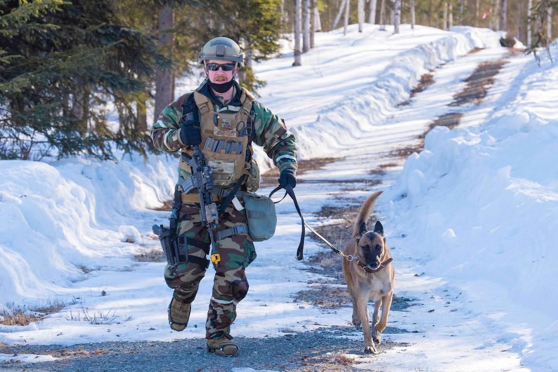 An airman runs alongside a dog down a road.