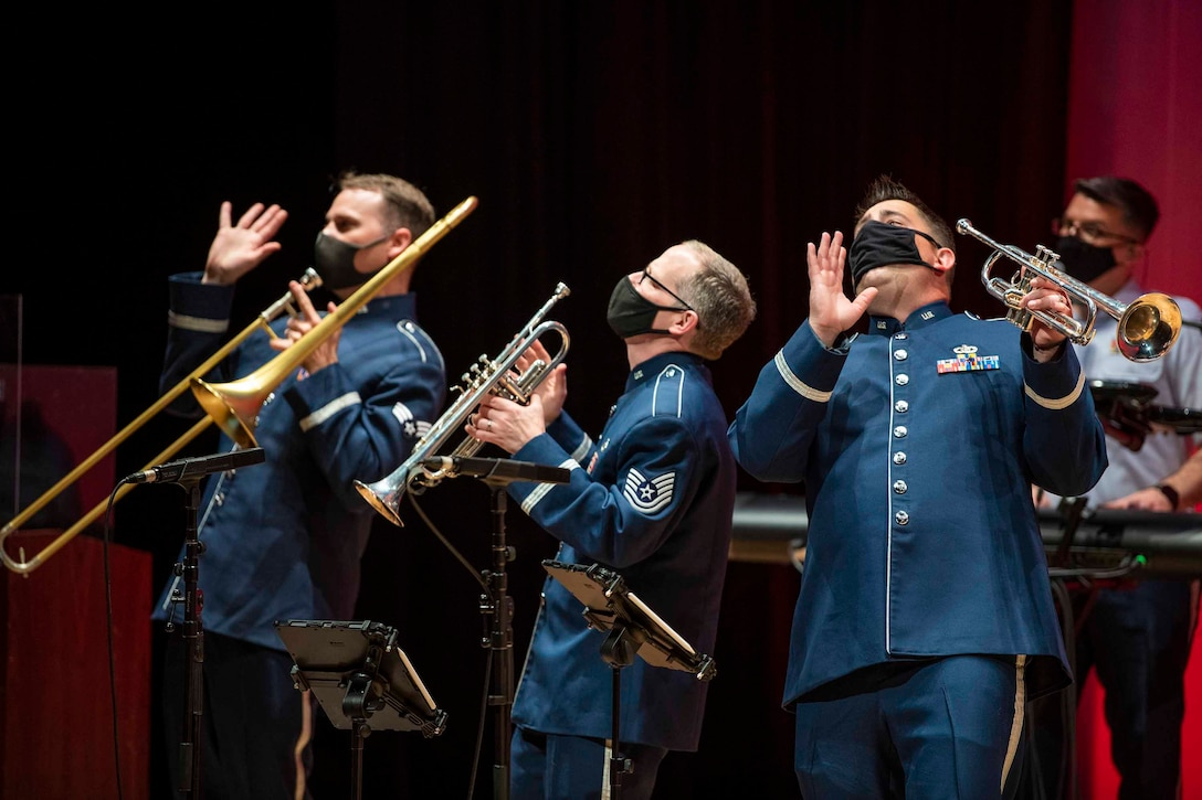 Three airmen stand on a stage wearing face masks and holding instruments.
