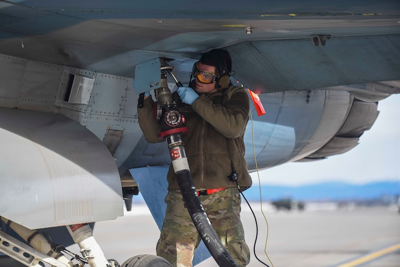 Senior Airman Shane Weber, 18th Aggressors Squadron avionics technician, refuels an F-16 Fighting Falcon, April 13, 2021, on Eielson Air Force Base, Alaska. Airmen trained during Arctic Gold 21-2 to accomplish multiple duties on the flightline, making our force more flexible during rapid deployment operations. (U.S. Air Force photo by Senior Airman Keith Holcomb)