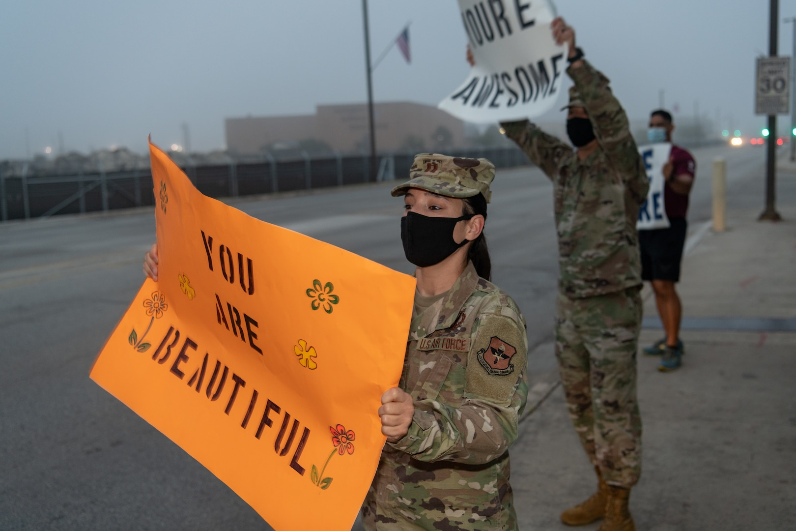U.S. Air Force Capt. Brandy Dorrough (front), assistant director of the 323rd Training Squadron, and Tech Sgt. Lee Fast, interim 1st Sgt. for the 323rd Training Squadron, greet cars during the We Care Day event, April 16th, 2021, at Joint Base San Antonio-Lackland, Texas.