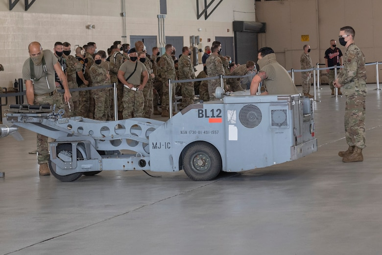 Photo of Airmen preparing to lift a munition
