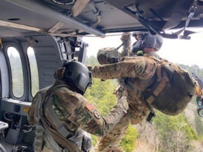 Tennessee National Guard Sgt. 1st Class Tracy Banta begins hoist operations, descending from a Black Hawk helicopter to a stroke victim who was hiking on the Appalachian Trail in Great Smoky Mountains National Park April 15, 2021. The patient was flown to a hospital in Knoxville.