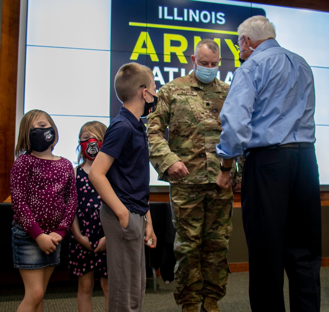 Family of newly promoted Lt. Col. Michael Barton, of Greenview, Illinois, children Bryer, Scarlett and Rhett, and uncle, Neil Tousley, tack on new rank during Barton's promotion ceremony April 5 at Camp Lincoln in Springfield, Illinois.