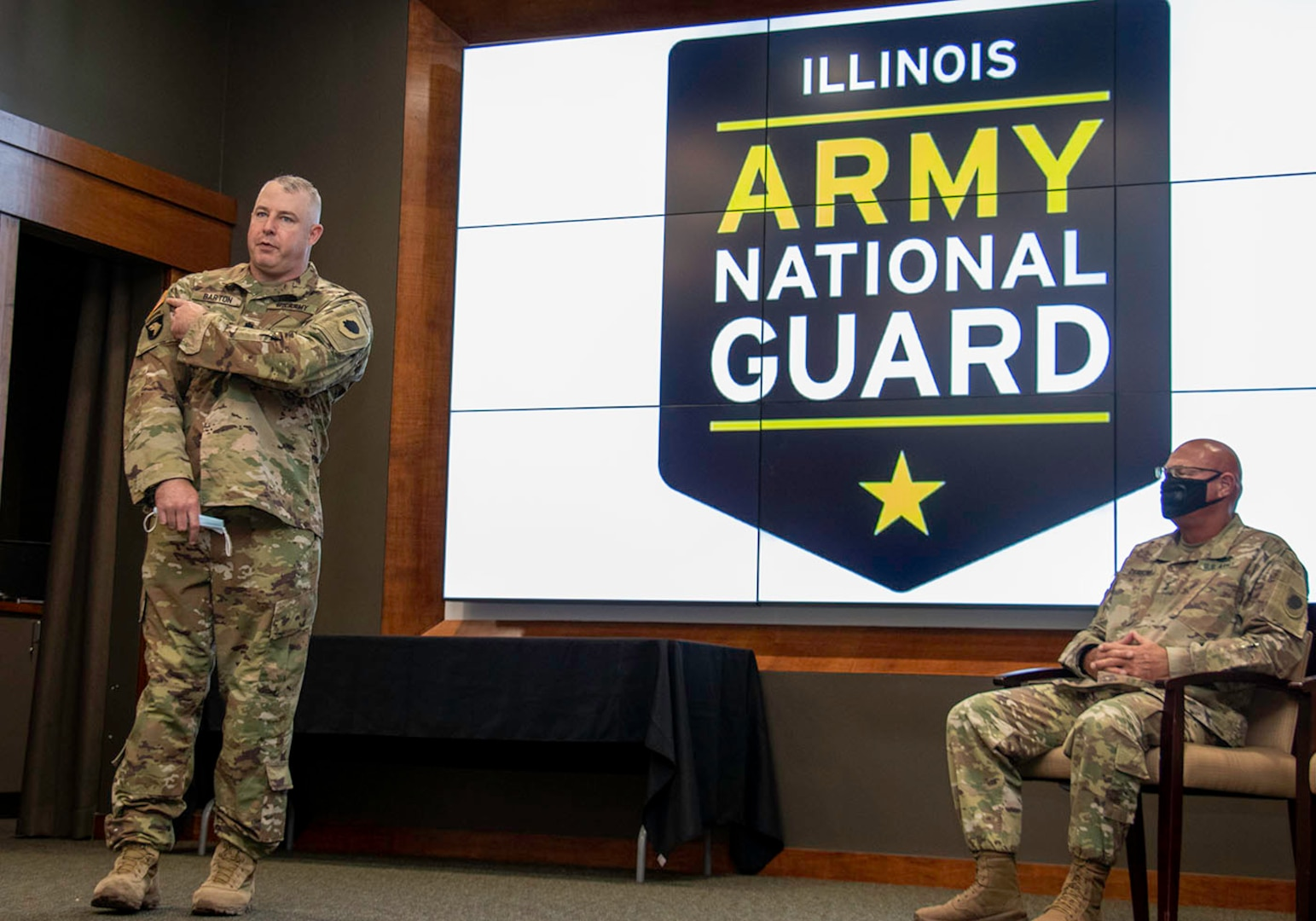 Newly promoted Lt. Col. Michael Barton, of Greenview, Illinois, points to the United States flag on his uniform to illustrate each member of the Illinois National Guard is an ambassador regardless of their reason for serving.
