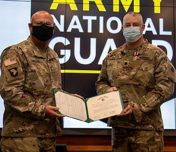 Newly promoted Lt. Col. Michael Barton, of Greenview, Illinois, (right) receives the Meritorious Service Medal from Maj. Gen. Michael R. Zerbonia, Assistant Adjutant General – Army, Illinois National Guard and Commander, Illinois Army National Guard, for Barton's work as the Assistant to the Chief of Staff, Illinois Army National Guard.