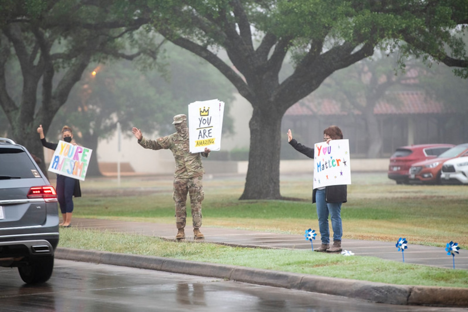 Volunteers hold signs in support of the We Care Day event April. 16, 2021, at Joint Base San Antonio-Randolph, Texas. The event was in support of Month of the Military Child and Child Abuse awareness month.