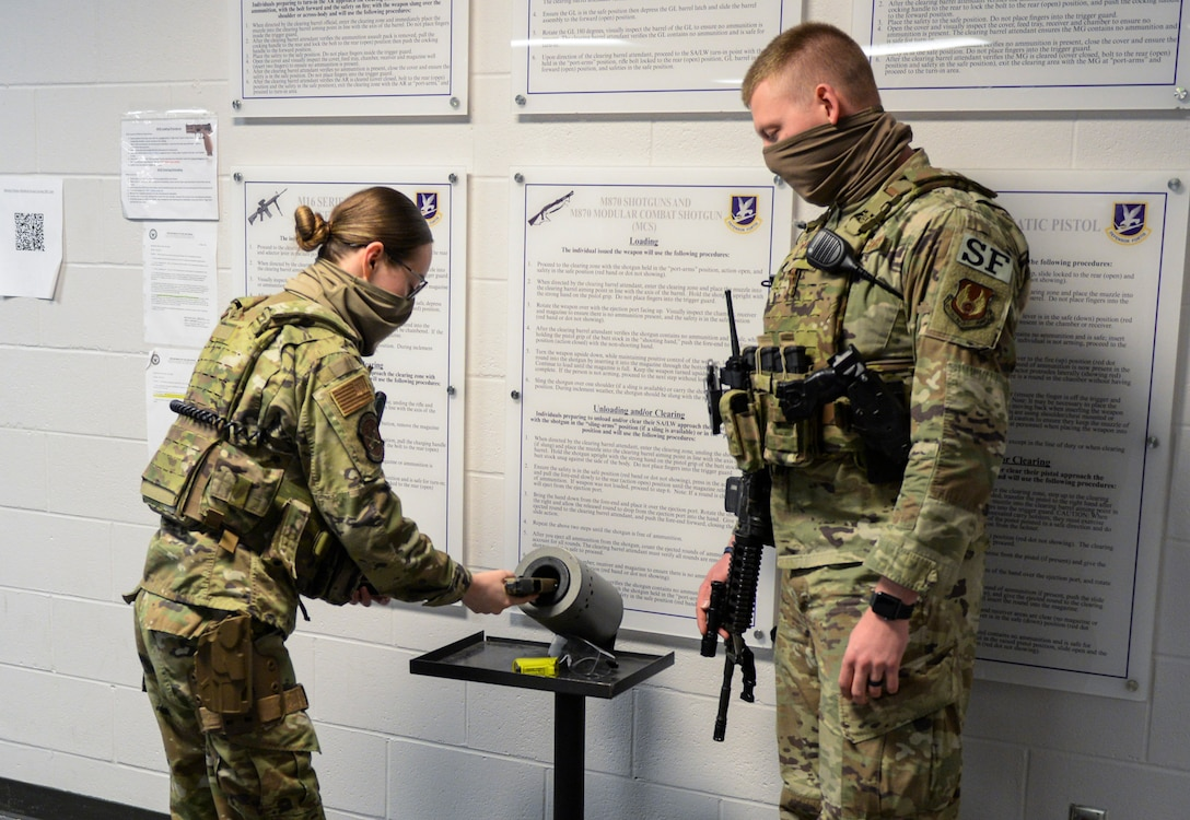 U.S. Air Force Airman 1st Class Iliana Arroyo, 88th Security Forces Squadron patrolman, loads a magazine into her M9 handgun, as Senior Airman Kyle Brown, 88th SFS base defense operations center controller, watches, March 16, 2021 at Wright-Patterson Air Force Base, Ohio. Security Forces members are responsible for providing base defense, as well as providing law enforcement on the installation. (U.S. Air Force photo by Wesley Farnsworth)