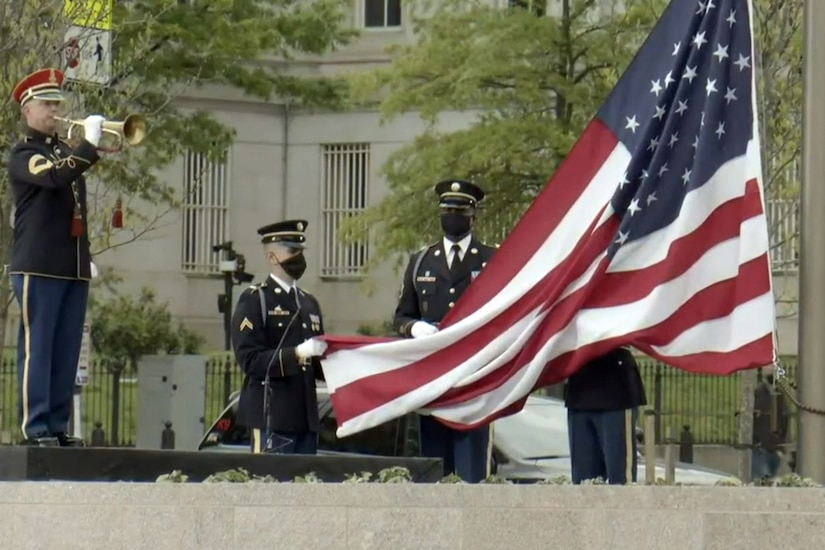 A man in a military uniform plays an instrument, while nearby, other men in military uniforms prepare to raise a large American flag.