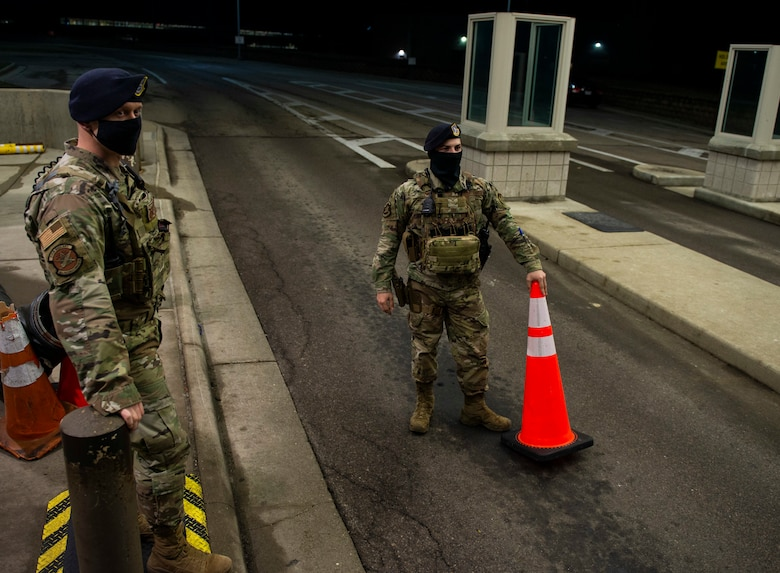 U.S. Air Force Staff Sgt. Jacob Swisher, 88th Security Forces Squadron base defense operations center controller, watches as a vehicle begins its approach to the gate as Airman 1st Class Jadon Dix, 88th SFS entry controllers and alarm monitor, prepares to remove a traffic cone at gate 19B, March 16, 2021 at Wright-Patterson Air Force Base, Ohio. Security Forces members are responsible for providing base defense, as well as providing law enforcement on the installation. (U.S. Air Force photo by Wesley Farnsworth)