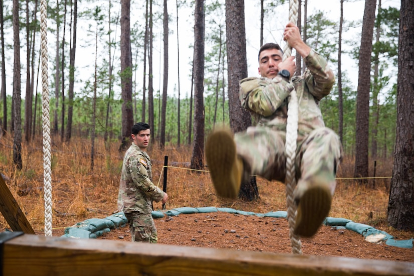 A soldier swings forward from a rope. Another soldier looks on in the background.