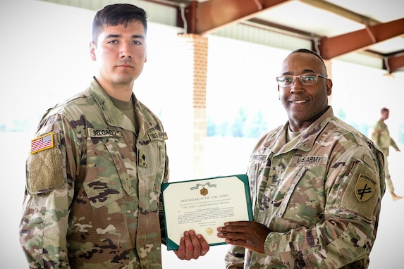 """U.S. Army Reserve Spc. Jaime Delgado, left, a civil affairs specialist with the 352nd Civil Affairs Command, is awarded an army commendation medal from Command Sgt. Maj, Petter Trotter, the senior enlisted leader of United States Army Civil Affairs and Psychological Operations Command (Airborne), for being named Soldier of the Year during the 2021 U.S. Army Civil Affairs and Psychological Operations Command (Airborne) Best Warrior Competition at Fort Jackson, S.C., April 10, 2021. The USACAPOC(A) BWC is an annual competition that brings in competitors from across USACAPOC(A) to earn the title of """"Best Warrior."""" BWC tests the Soldiers' individual ability to adapt and overcome challenging scenarios and battle-focused events, testing their technical and tactical skills under stress and extreme fatigue."""