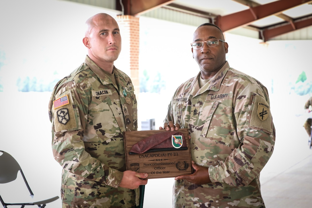 """Staff Sgt. Jonathan Chacon, left, a civil affairs specialist with the 426th Civil Affairs Battalion (Airborne), is awarded a plaque from Command Sgt. Maj, Petter Trotter, the senior enlisted leader of United States Army Civil Affairs and Psychological Operations Command (Airborne), for being named NCO of the Year during the 2021 U.S. Army Civil Affairs and Psychological Operations Command (Airborne) Best Warrior Competition at Fort Jackson, S.C., April 10, 2021. The USACAPOC(A) BWC is an annual competition that brings in competitors from across USACAPOC(A) to earn the title of """"Best Warrior."""" BWC tests the Soldiers' individual ability to adapt and overcome challenging scenarios and battle-focused events, testing their technical and tactical skills under stress and extreme fatigue."""