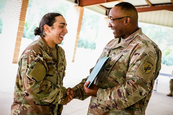 """Staff Sgt. Natalie Tedesco, left, a psychological operations specialist with the 303rd Psychological Operations Company, receives an award from Command Sgt. Maj, Petter Trotter, the senior enlisted advisor of U.S. Army Civil Affairs and Psychological Operations Command (Airborne), for competing during the 2021 U.S. Army Civil Affairs and Psychological Operations Command (Airborne) Best Warrior Competition at Fort Jackson, S.C., April 10, 2021. The USACAPOC(A) BWC is an annual competition that brings in competitors from across USACAPOC(A) to earn the title of """"Best Warrior."""" BWC tests the Soldiers' individual ability to adapt and overcome challenging scenarios and battle-focused events, testing their technical and tactical skills under stress and extreme fatigue."""