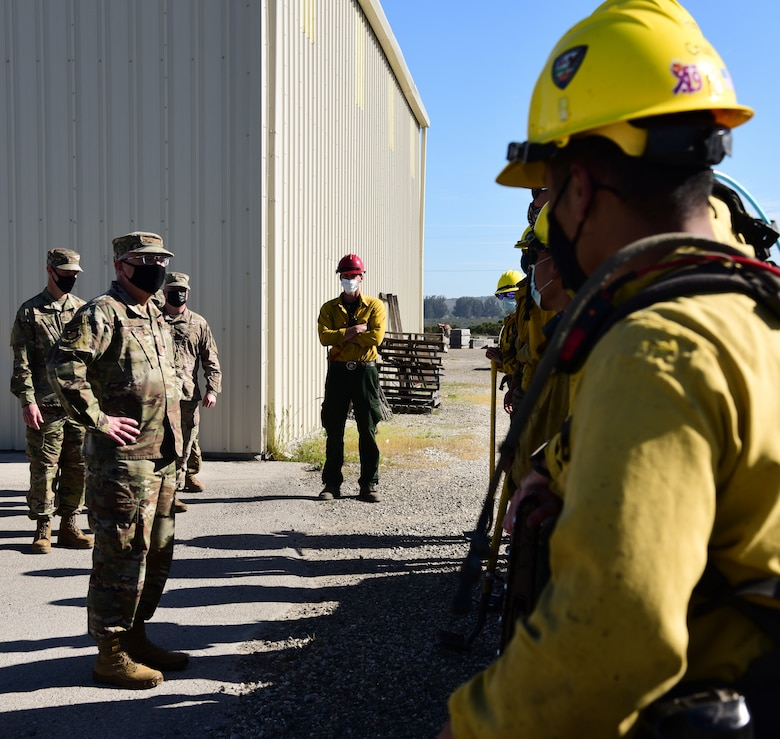 The 30th Space Wing Hotshot firefighters explain how the team extinguishes brush fires to Lt. Gen. John F. Thompson, U.S. Space Force's Space and Missile Systems Center commander, April 9, 2021, at Vandenberg Air Force Base, Calif. Due to Vandenberg AFB's location, wildland fires are a common occurrence during the summer months and the Hotshots play a major role in keeping the installation ready and able to continue the mission. (U.S. Space Force photo by Airman 1st Class Rocio Romo)