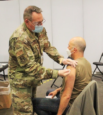 New York Air National Guard Lt. Col. John Reynolds, a registered nurse assigned to the 105th Airlift Wing, vaccinates John Giarratano at the Jacob K. Javits Convention Center in New York City April 12, 2021. The convention center serves as a mass vaccination site with more than 600 National Guard personnel assisting the state health department.