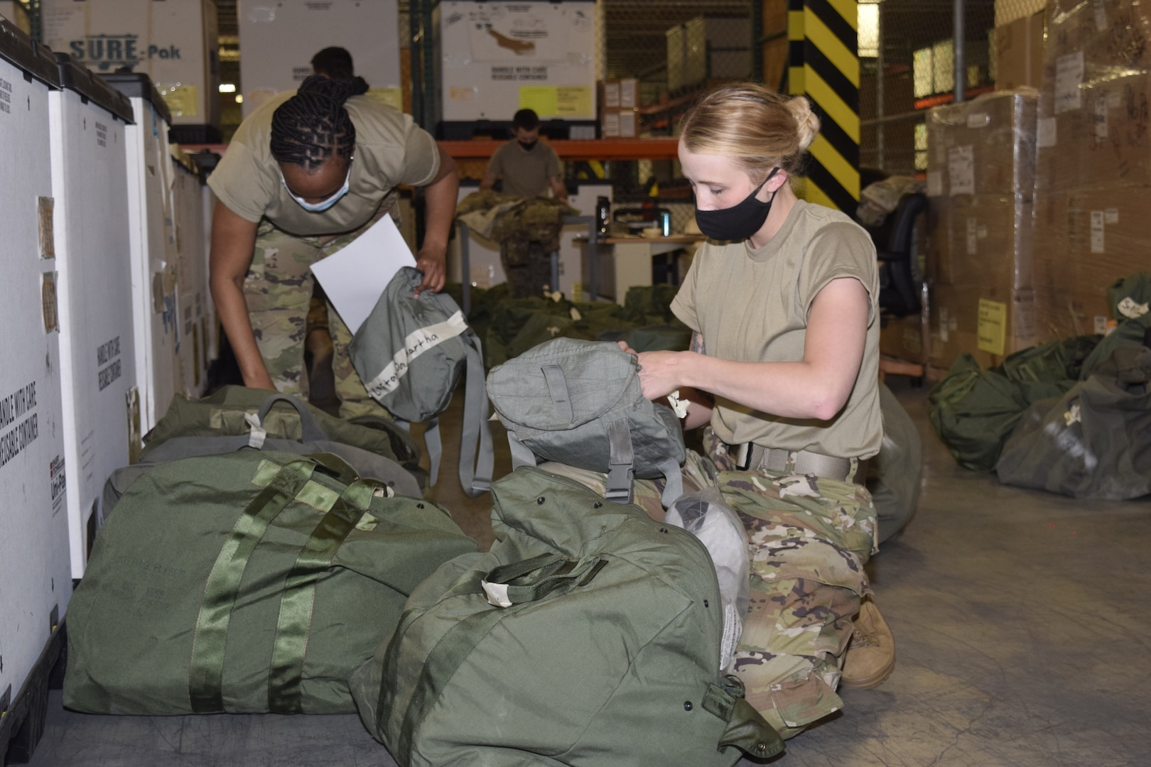Tech Sgt. Alicia Garvin, 433rd Force Support Squadron customer support NCO in charge, Staff Sgt. Alexandra Thompson, 433rd FSS customer support assistant, and Staff Sgt. Taylor Mogford, 433rd Logistics Readiness Squadron individual protective equipment supervisor (background), prepare and issue equipment for an upcoming exercise at Joint Base San Antonio-Lackland, Texas, April 7, 2021. The 433rd LRS contains 120 Airmen in eight Air Force career fields, who specialize in deployment planning, supply chain operations, fuels and transportation management. (U.S. Air Force photo by Senior Airman Brittany Wich)