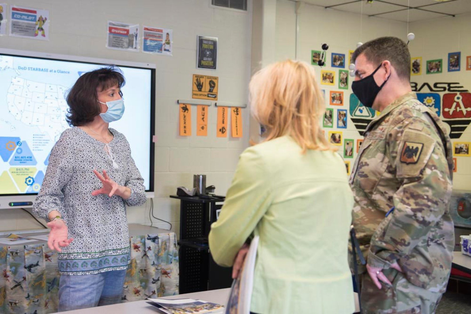 Sherra Triggs, left, director of STARBASE Martinsburg, speaks with U.S. Air Force Lt. Gen. Michael A. Loh, director, Air National Guard, and his wife Diane Loh, about teaching STARBASE curriculum through the COVID-19 pandemic, during their visit to the 167th Airlift Wing, West Virginia National Guard, at Shepherd Field Air National Guard Base in Martinsburg, West Virginia, March 9, 2021. During his visit, Loh received updates on the unit's current operations and response to the COVID-19 pandemic.