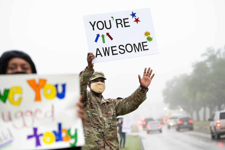 Command Master Chief Wendell Snider (middle) holds a signs in support of the We Care Day event April. 16, 2021, at Joint Base San Antonio-Randolph, Texas. The event was in support of Month of the Military Child and Child Abuse awareness month.